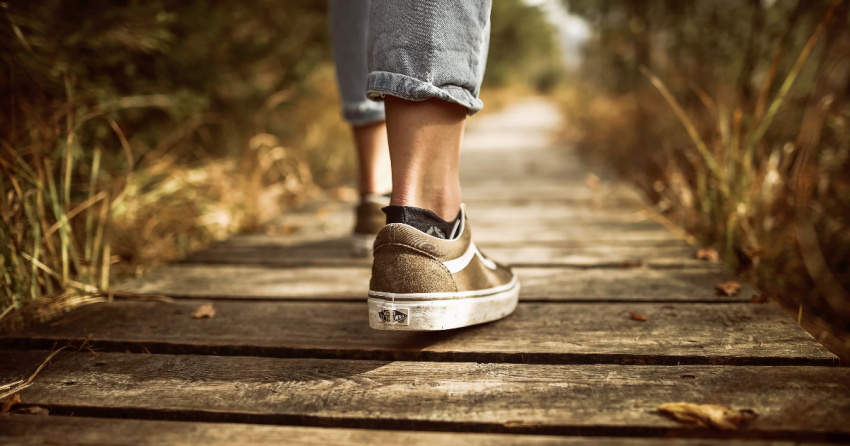 A student with jeans and tennis shoes steps out onto a long, wood bridge making a path into the distance