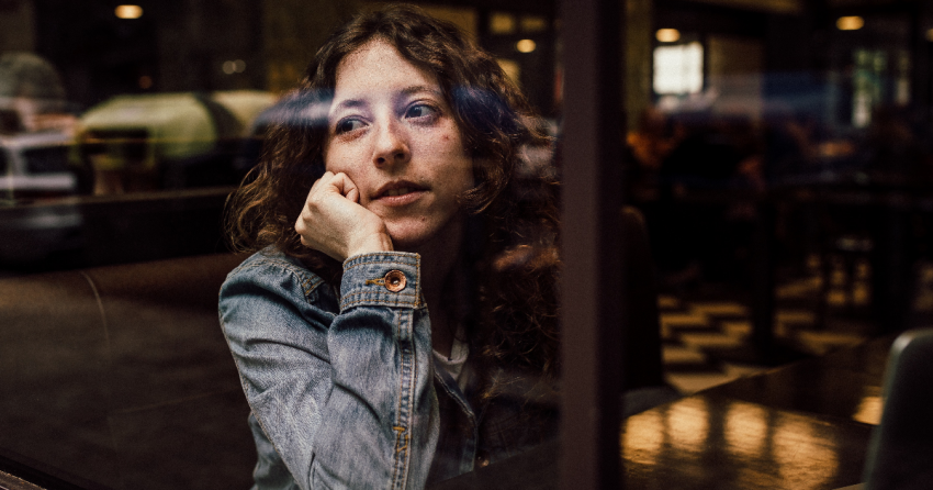 young woman stares listlessly out of a coffeeshop window