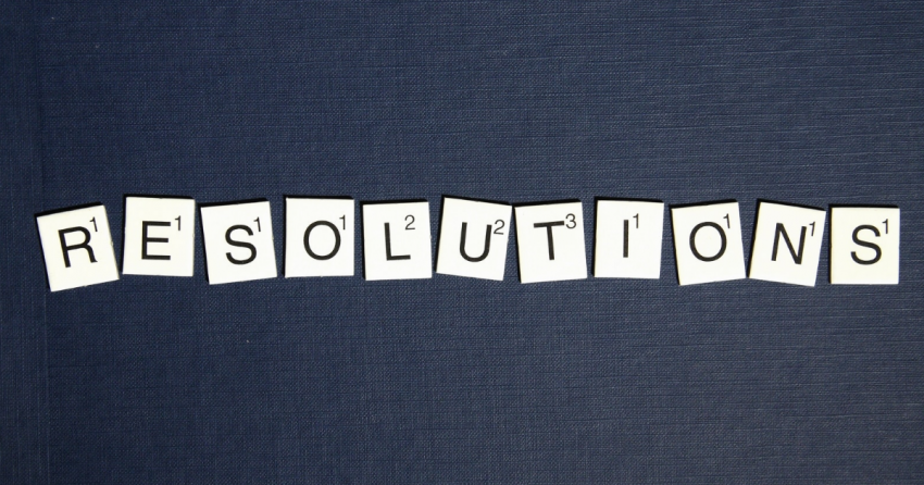 on a blue jean background, the word resolutions is spelled out in scrabble tiles